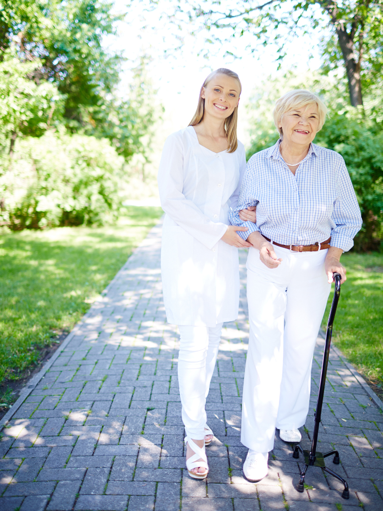 Pretty nurse and senior patient walking out in summer